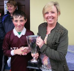 Athea U10 Captain Michael Tierney accepting the cup on behalf of Athea team from Sinead Roche in Foynes on Saturday last
